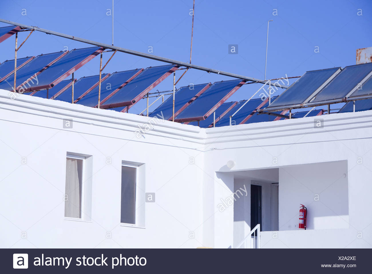 Solar water heating panels on the roof of a launderette in Teos, Western Turkey. - Stock Image