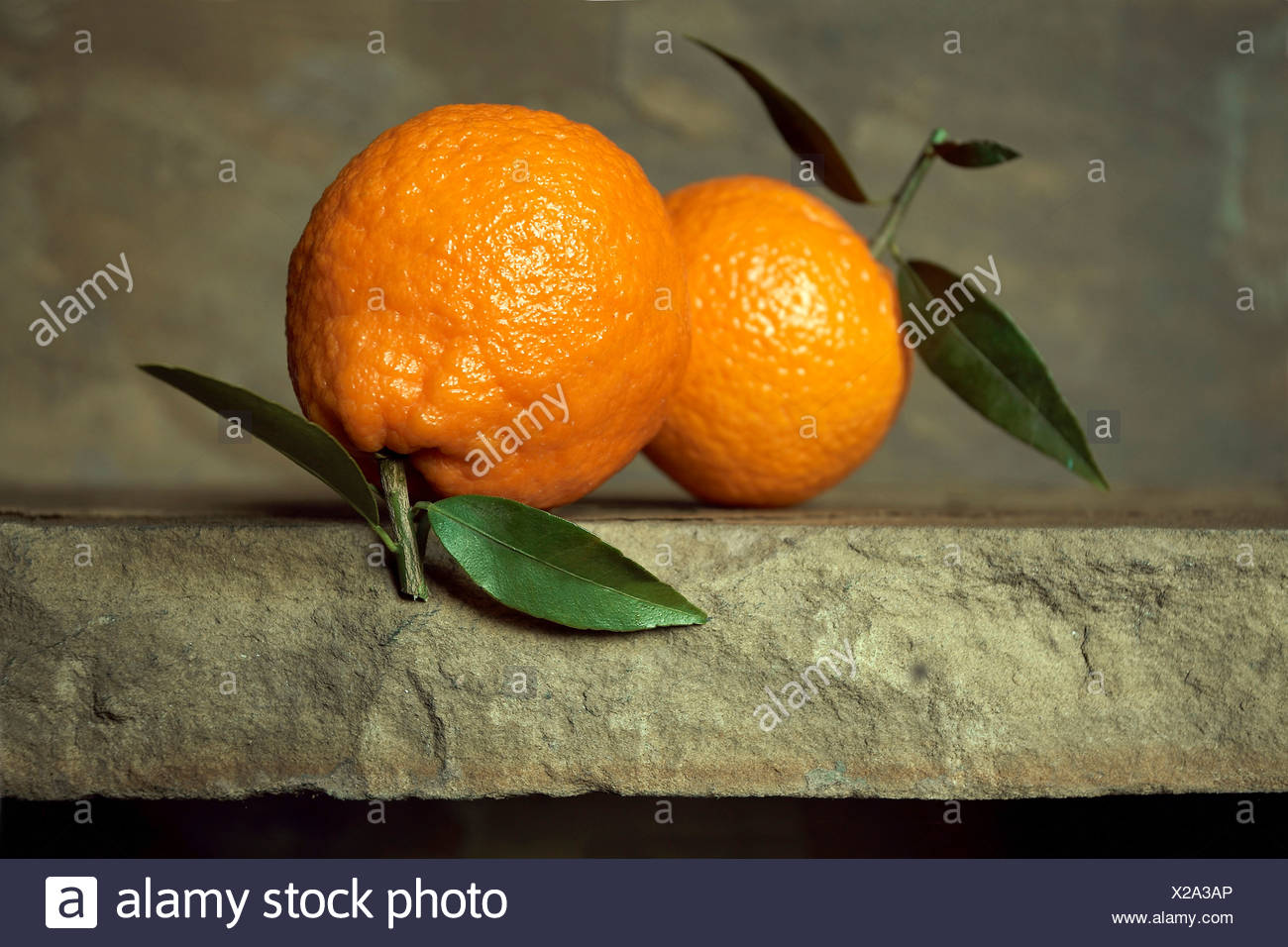 Two oranges with leaves on stone background - Stock Image