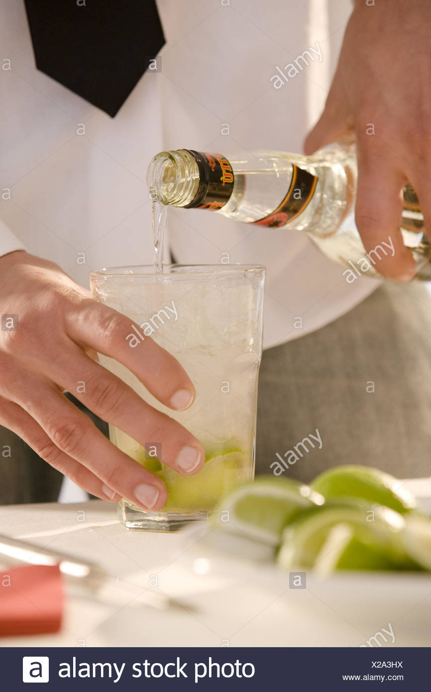 Barkeepers, detail, hands, cocktail, Caipirinha, prepare, glass, limes, ice, sugarcane schnapps, fill up, Stock Photo