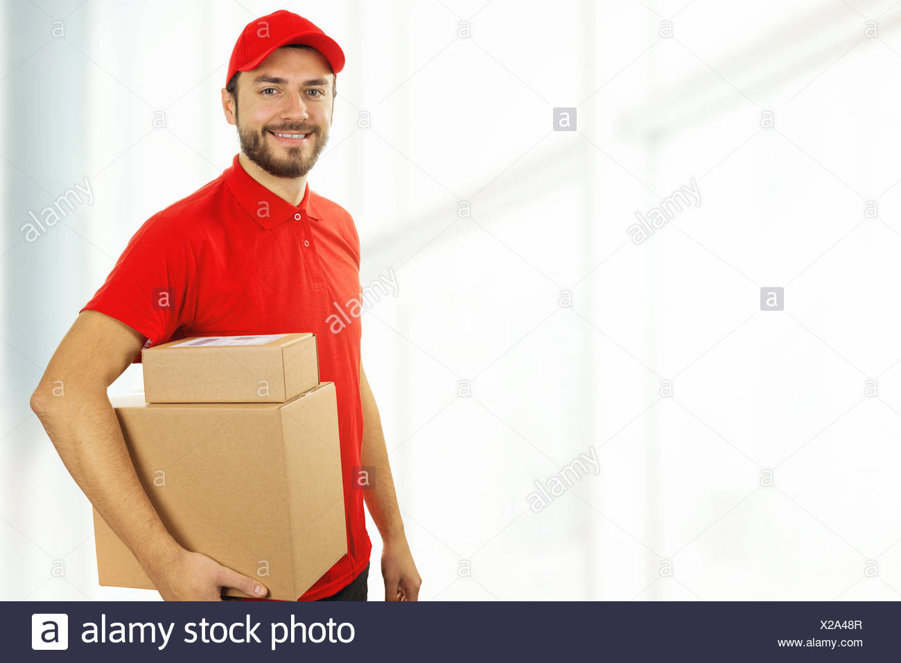 delivery man with cardboard boxes standing in office. copy space - Stock Image