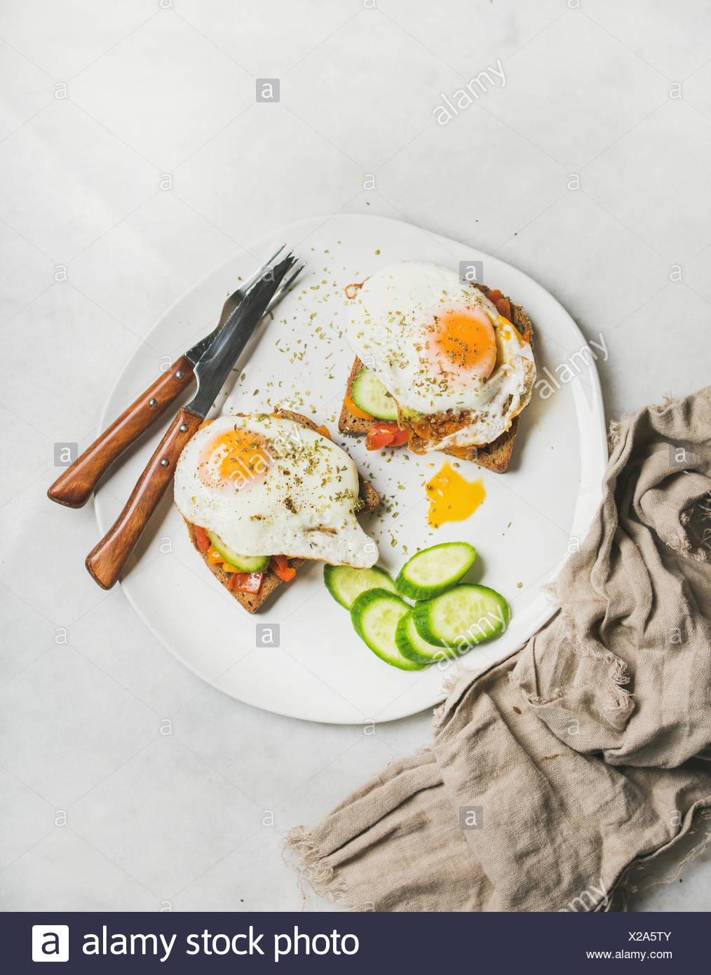 Breakfast toast with fried eggs with vegetables on white plate over grey marble background, top view. Healthy, clean eating, dieting food concept - Stock Image