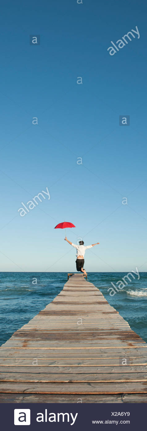 Man jumping on pier with umbrella, rear view Stock Photo