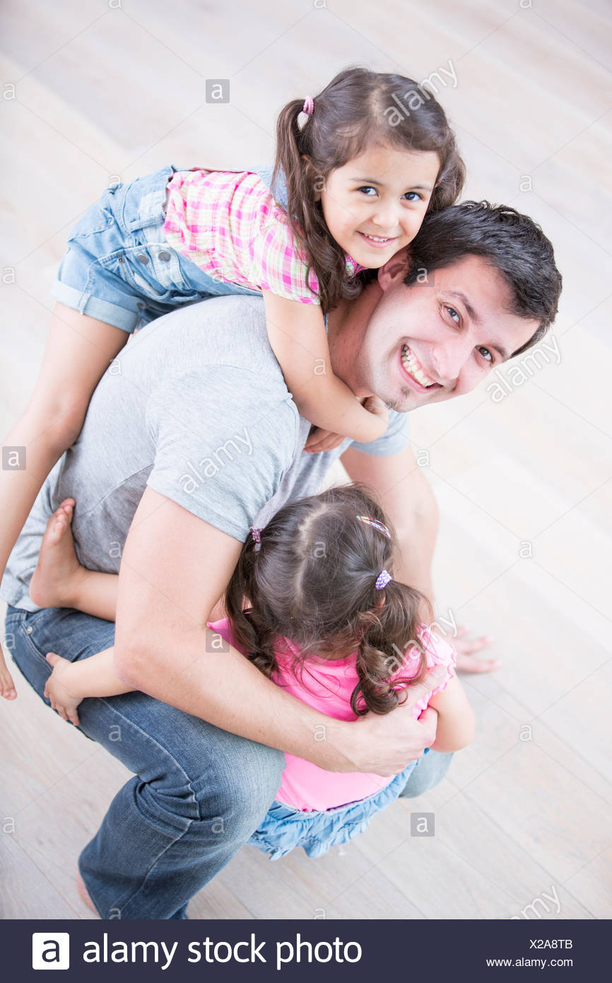 High angle portrait of playful father carrying girls at home Stock Photo