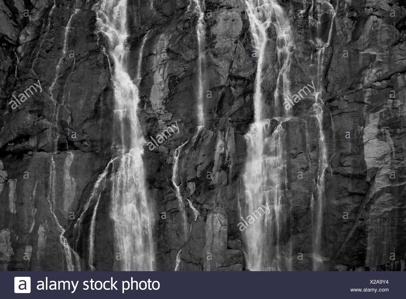 A waterfall cascades over rock cliffs on the Juneau Ice Field in Southeast Alaska - Stock Image