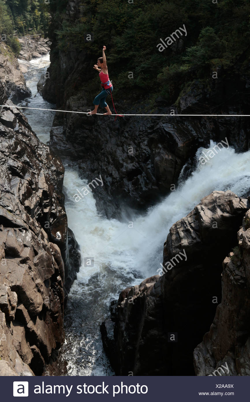 Female slackliner walking a highline over a waterfall - Stock Image