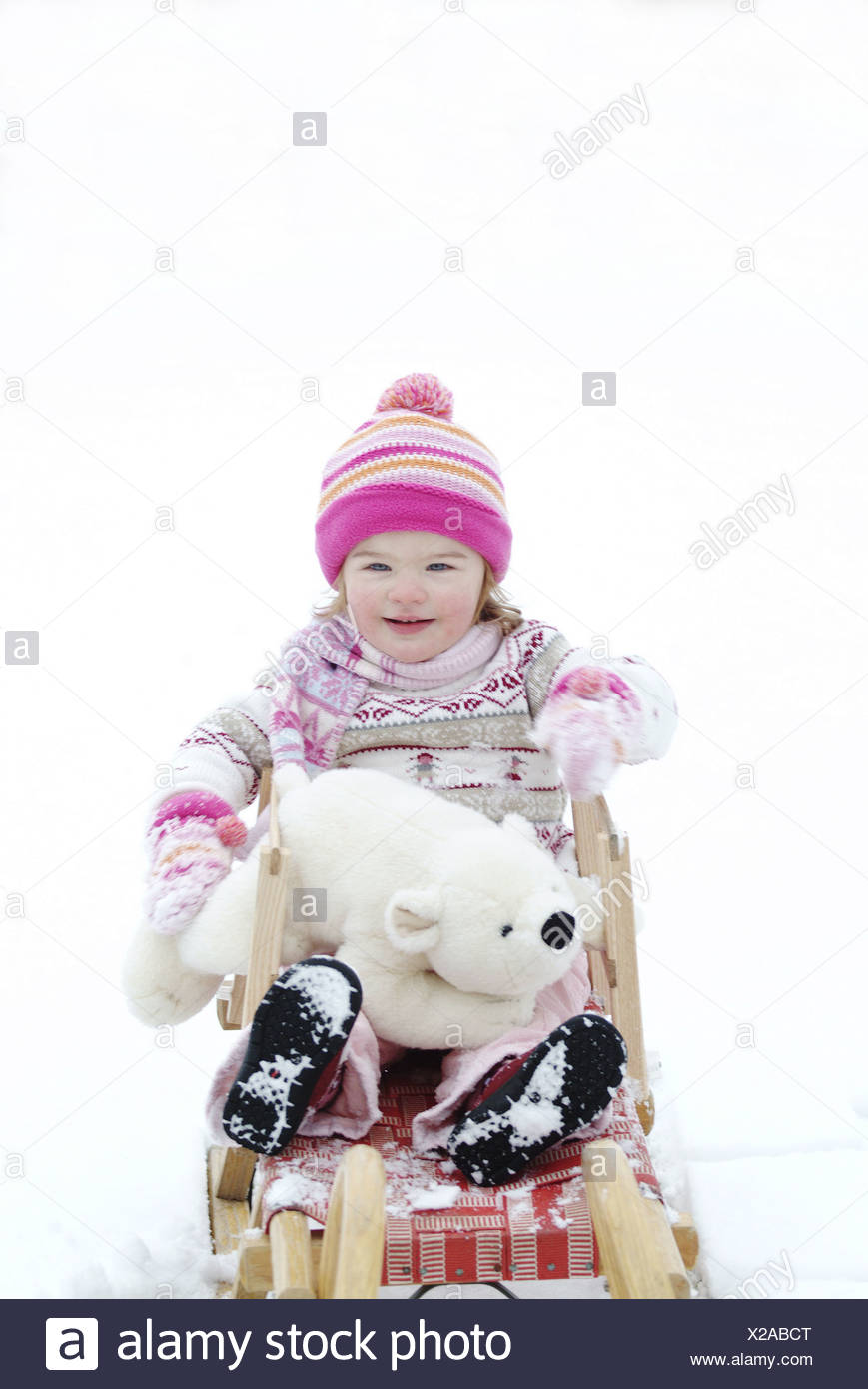 Child girls winter-clothing cheerfully material-animal 'polar bear' sled snow people toddler 2-4 years cap rope-cap headgear - Stock Image