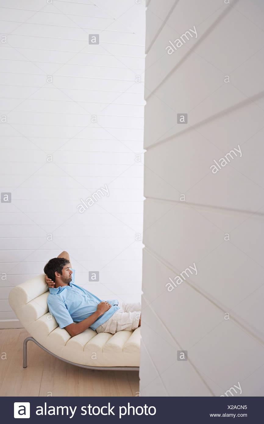 Man lying in reclining chair, half length - Stock Image