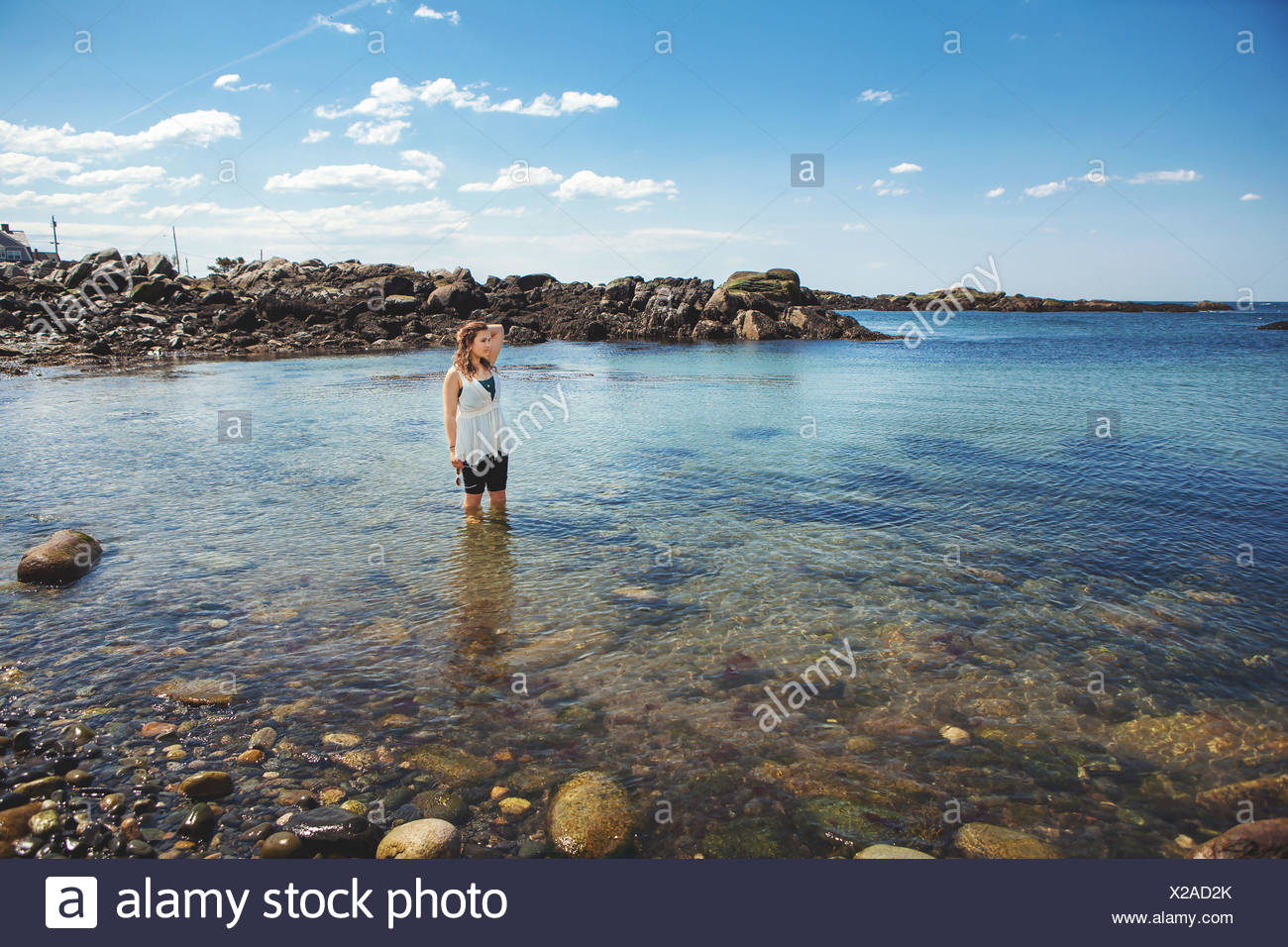 Young woman in the sea at the rocky coastal beach in Biddeford, Maine, USA - Stock Image