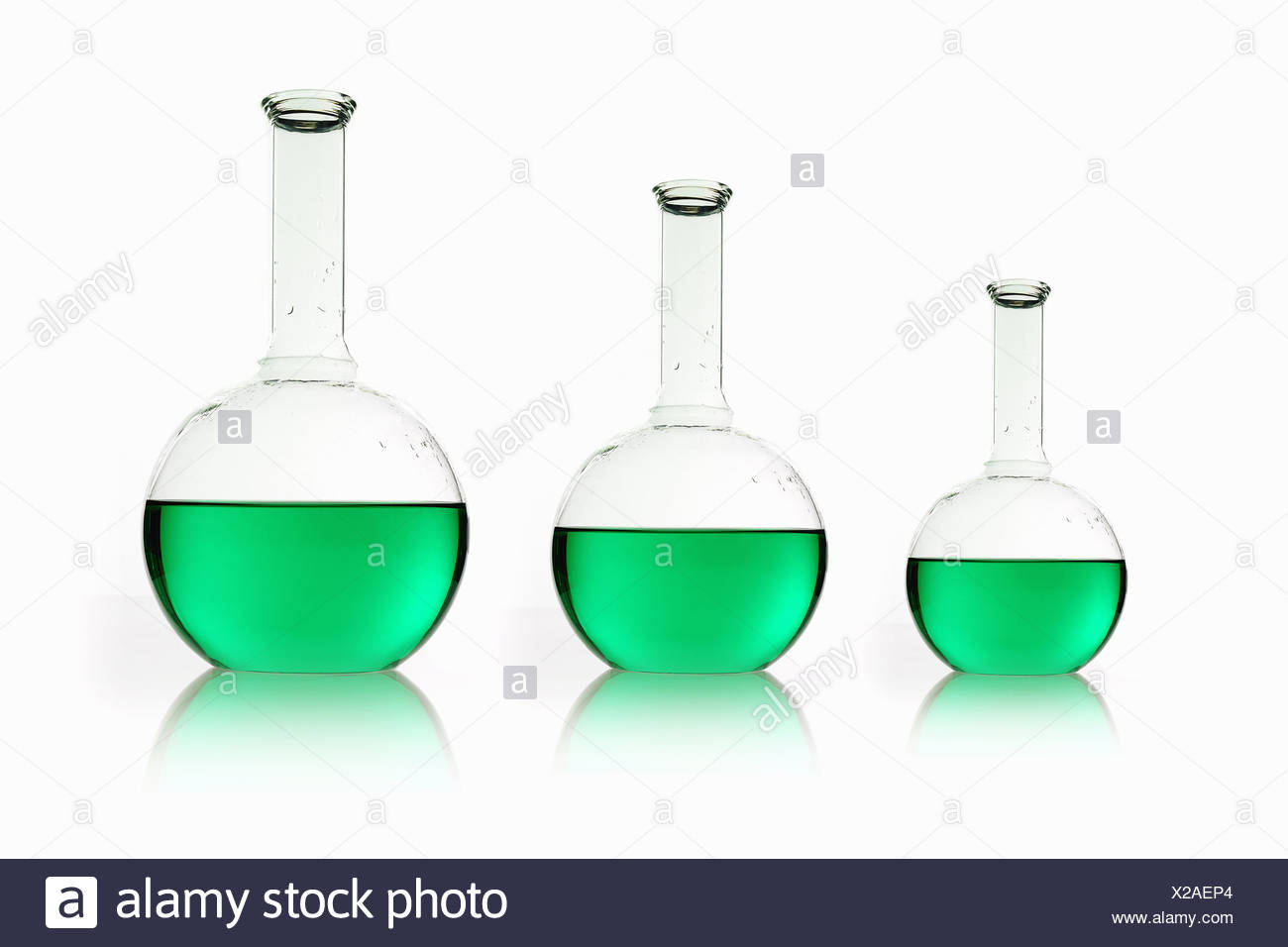Three rounded shaped scientific chemical flasks holding green liquid, arranged in size order. - Stock Image