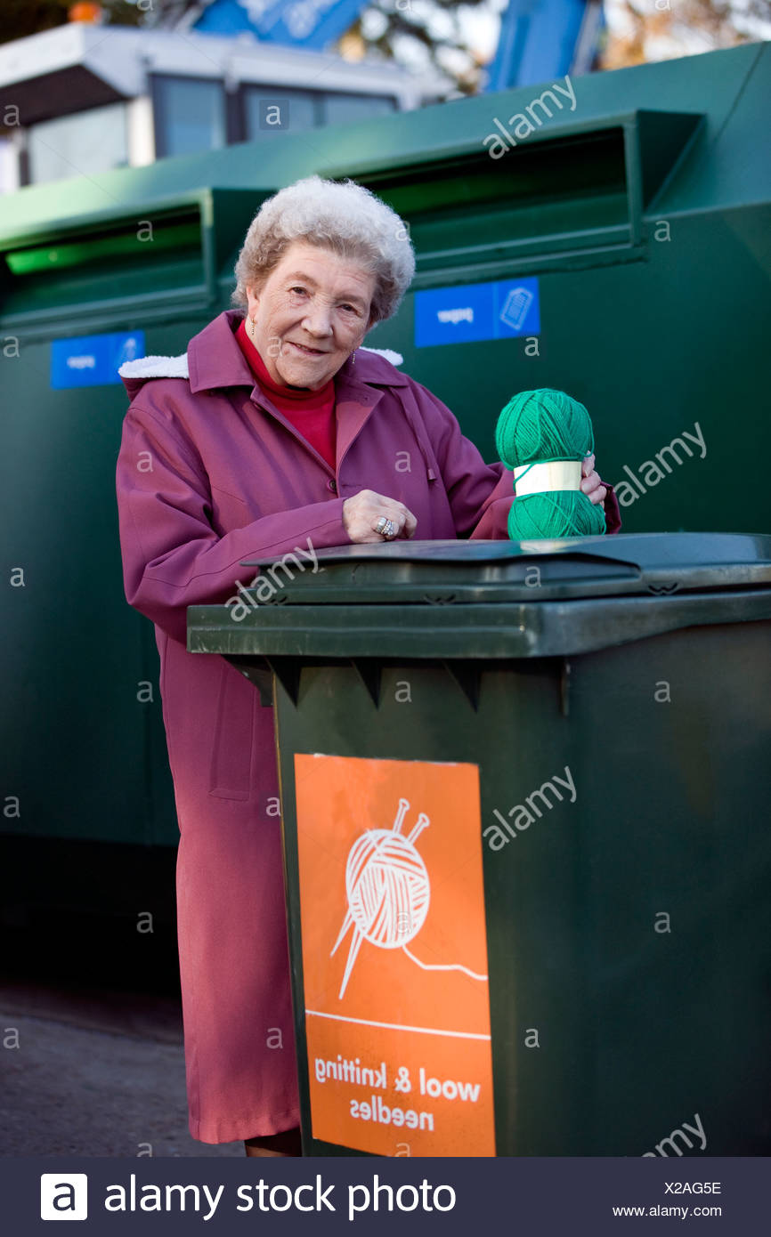 A senior woman recycling a ball of wool - Stock Image