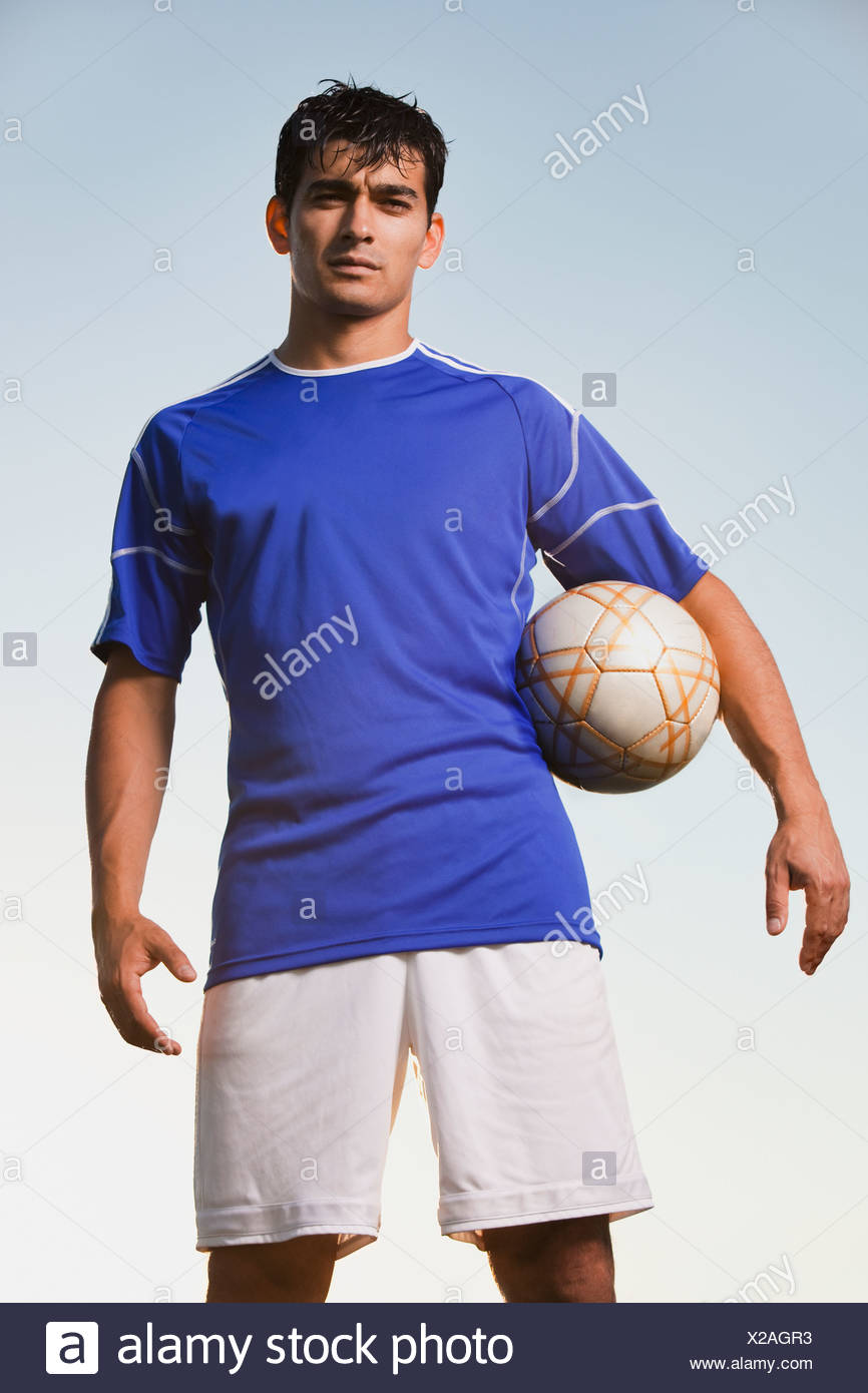 Soccer player holding ball - Stock Image