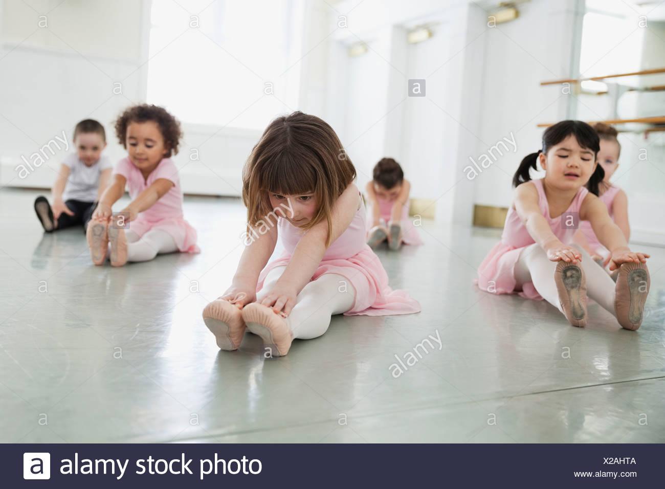 Children doing stretching exercises in ballet studio - Stock Image