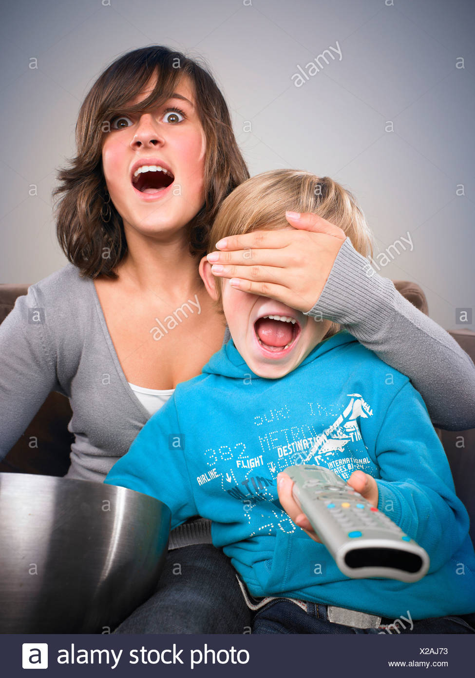 Brother and sister watching TV - Stock Image