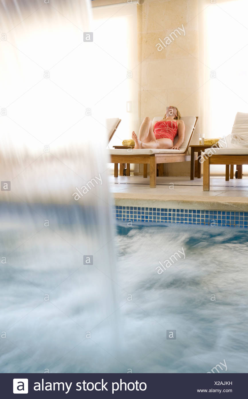 Woman laying on lounge chair near spa swimming pool with waterfall Stock Photo