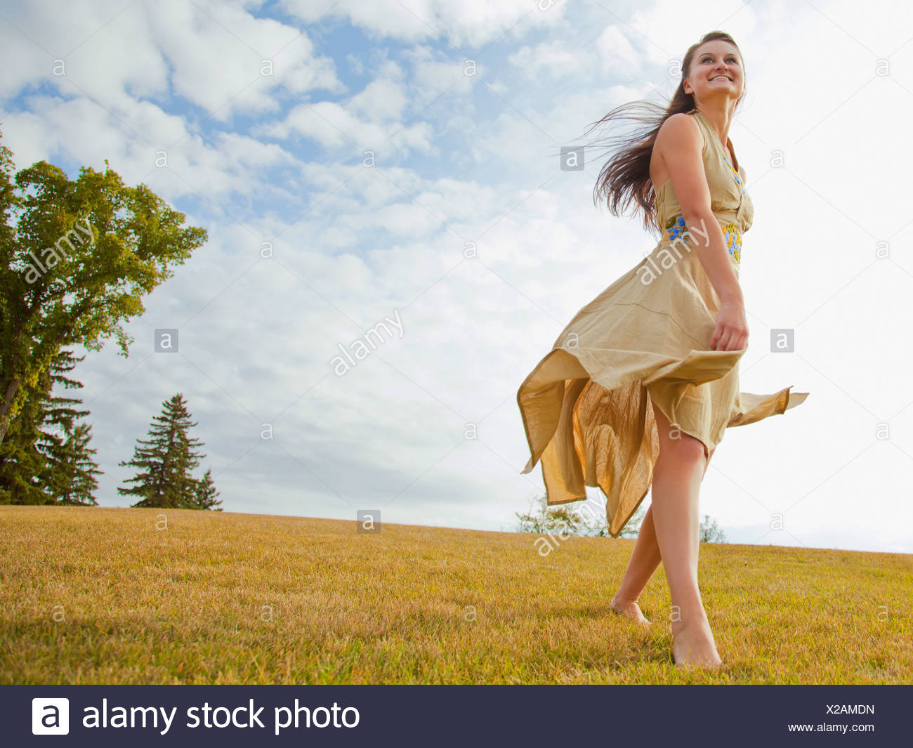 c450d887021a5 Young Woman Dancing In The Park With A Flowing Dress; Edmonton, Alberta,  Canada