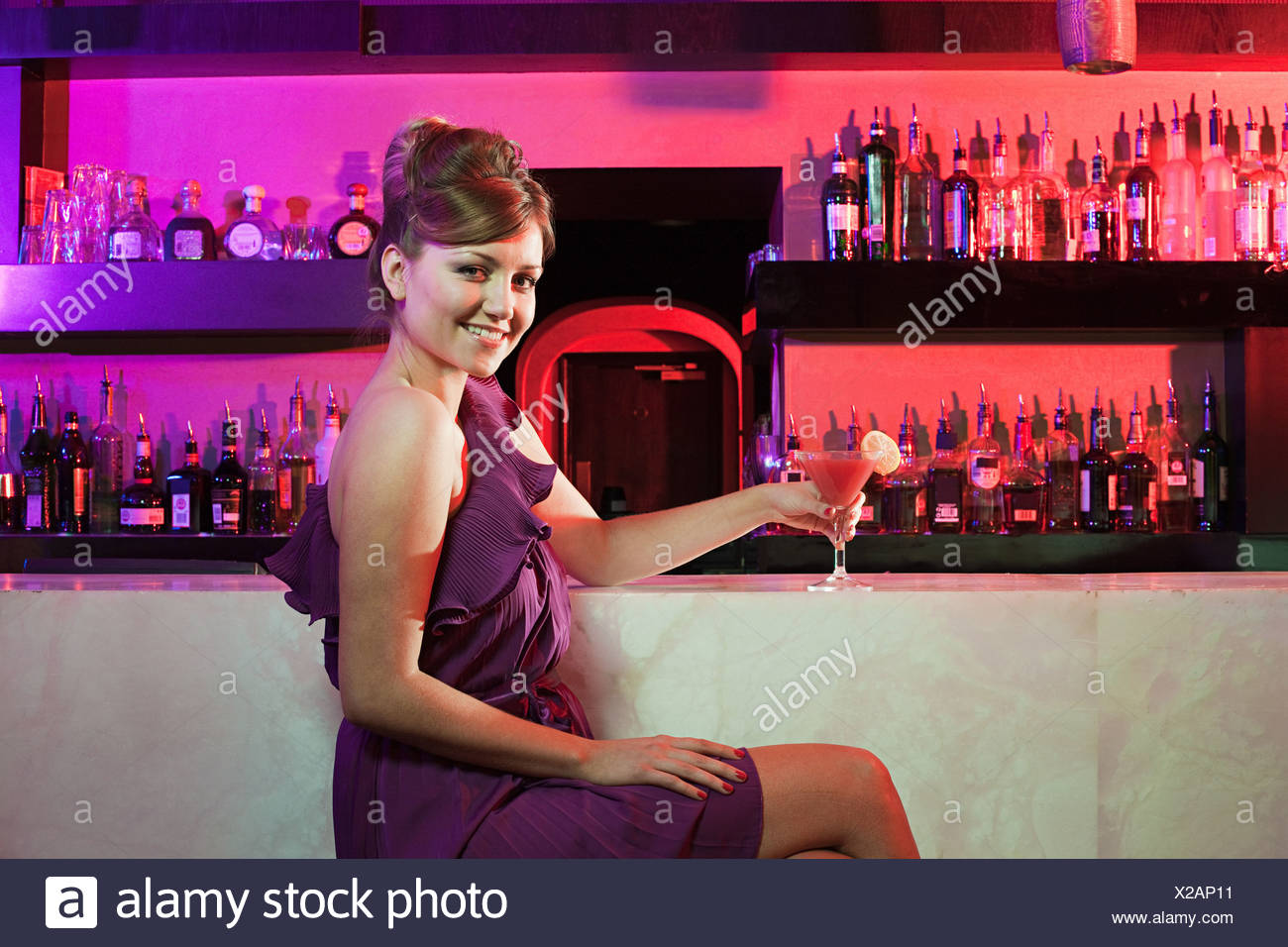 Happy young woman sitting at cocktail bar - Stock Image