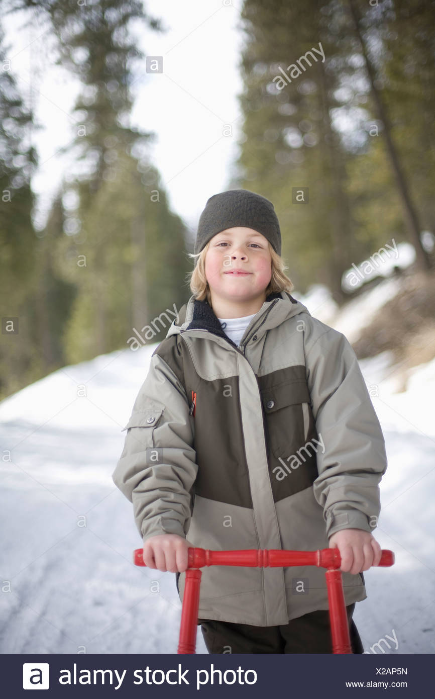 A portrait of a young boy and his sled outside on a snowy road. - Stock Image