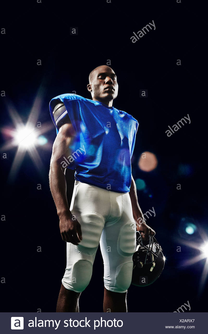 Portrait of american football player holding helmet Stock Photo