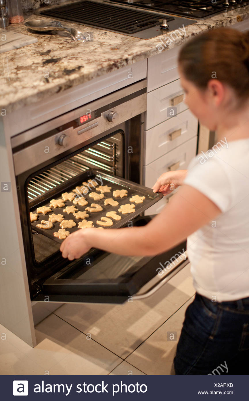 Teenage girl placing baking tray of biscuits in oven - Stock Image