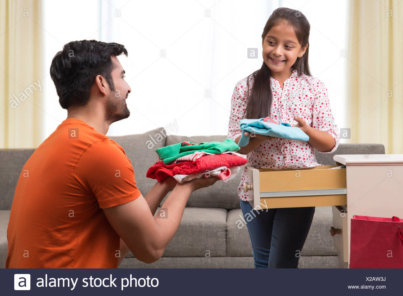 Daughter and father organizing clothes in cupboard - Stock Image