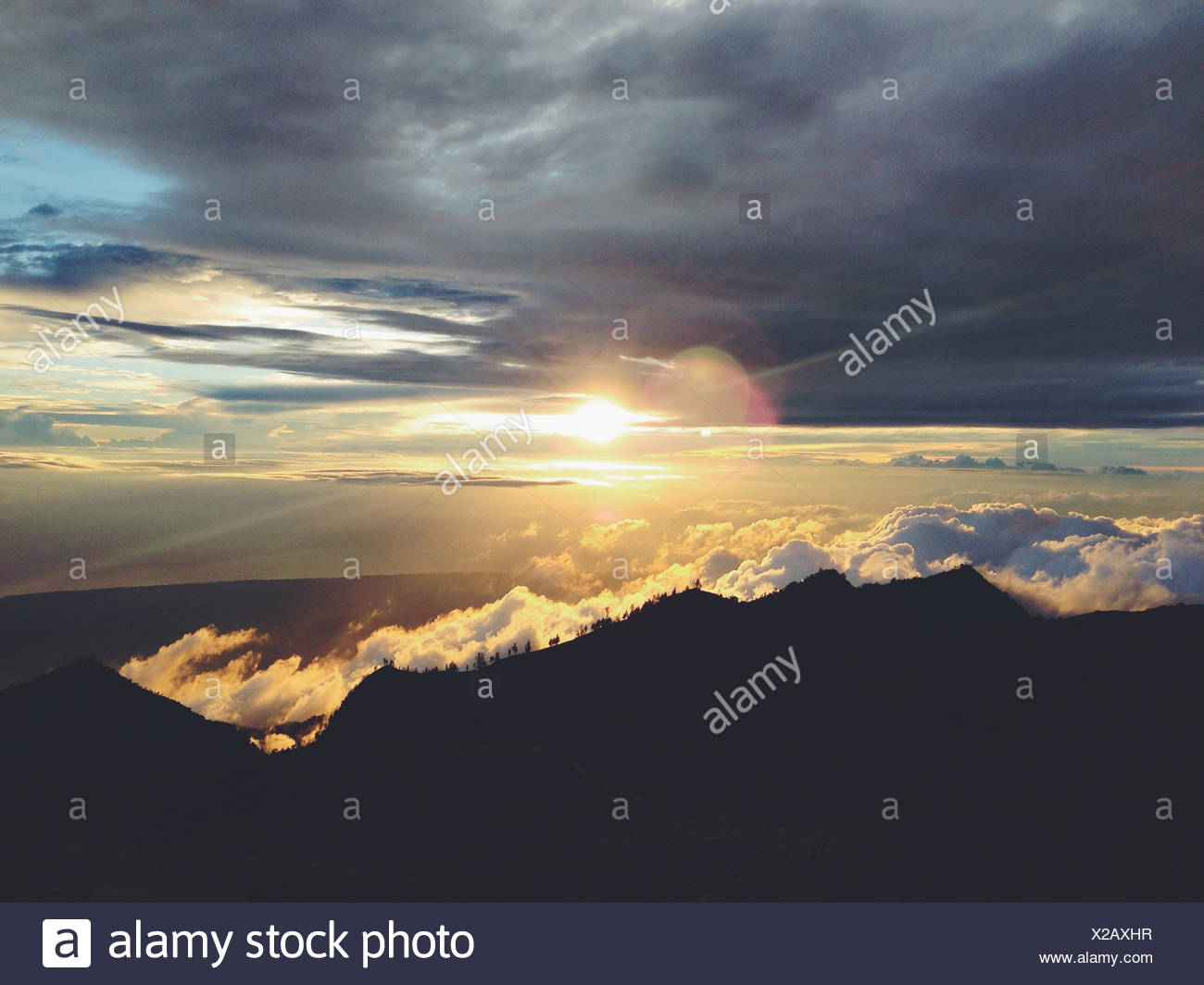 Sun peeping behind clouds - Stock Image