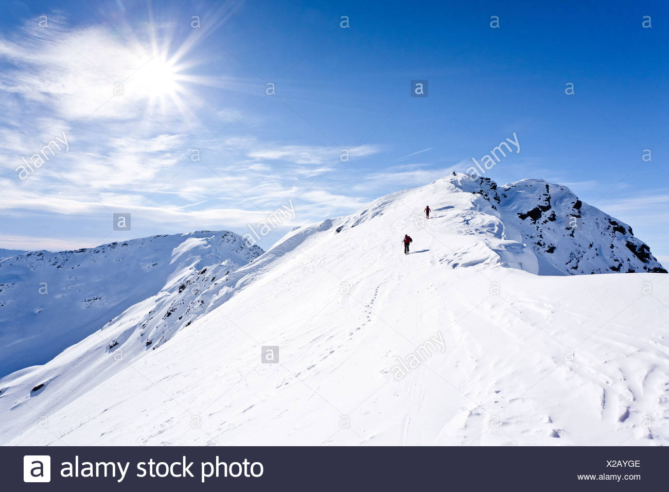 Ski mountaineers during ascent to Mt Hoertlahner above Durnholz walking across the summit ridge, Sarntal valley Stock Photo