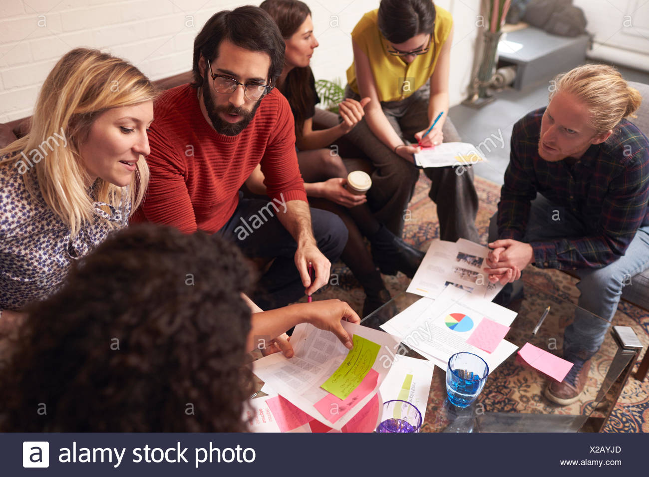 Designers Sitting On Sofa Having Creative Meeting In Office - Stock Image