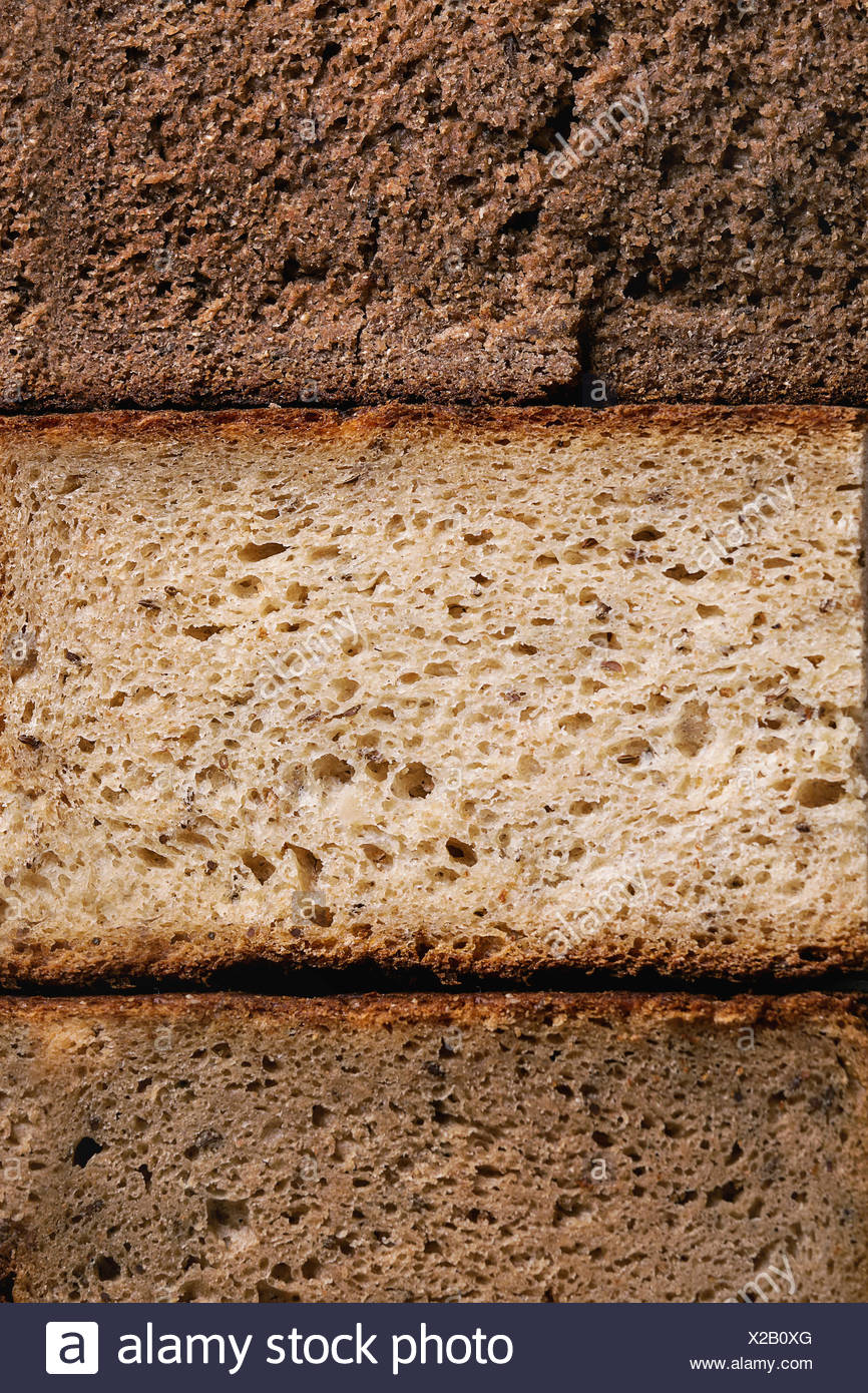 Variety loaves of sliced homemade rye bread whole grain. Top view, close up. Healthy eating food background - Stock Image