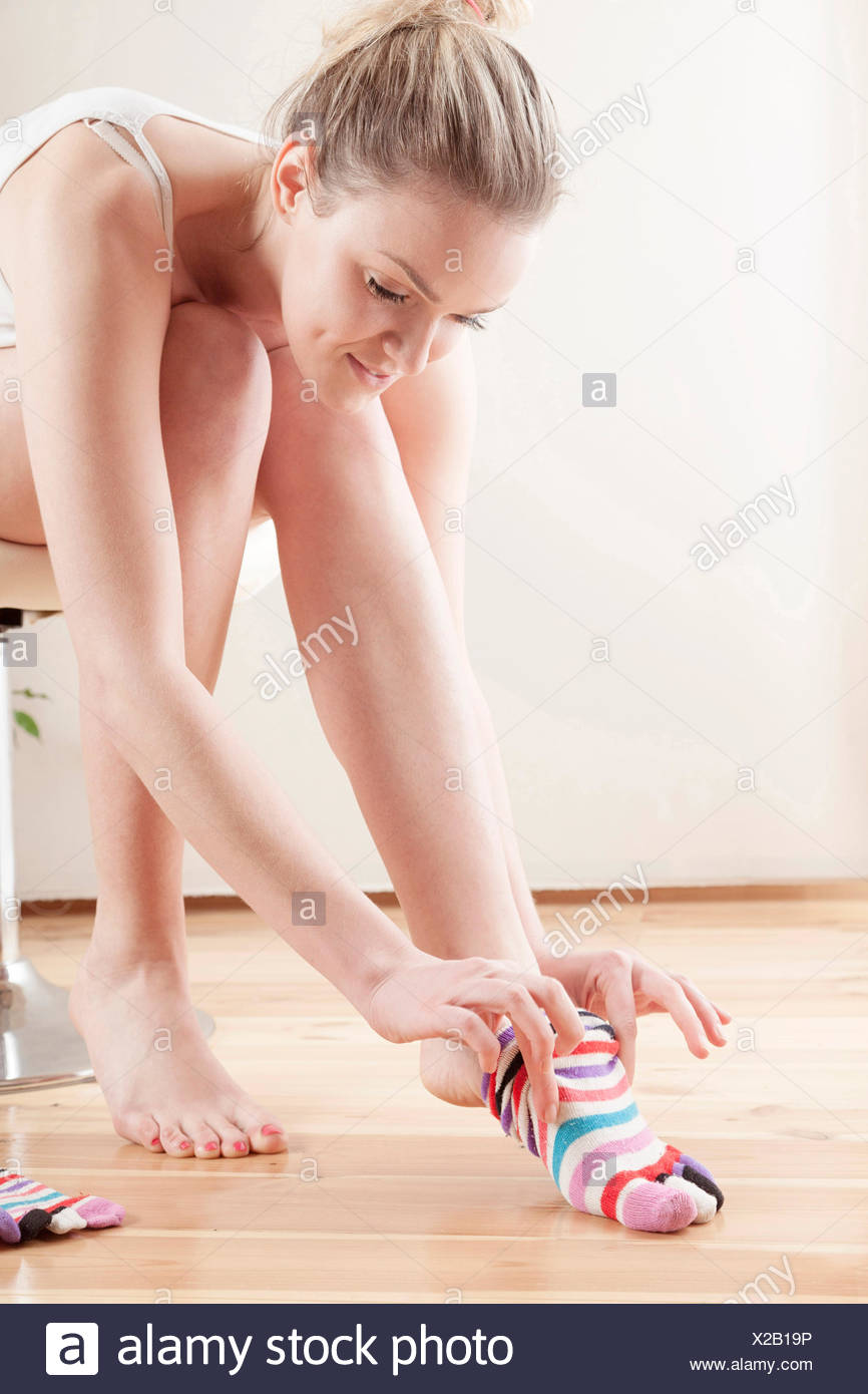 Young woman putting on socks - Stock Image