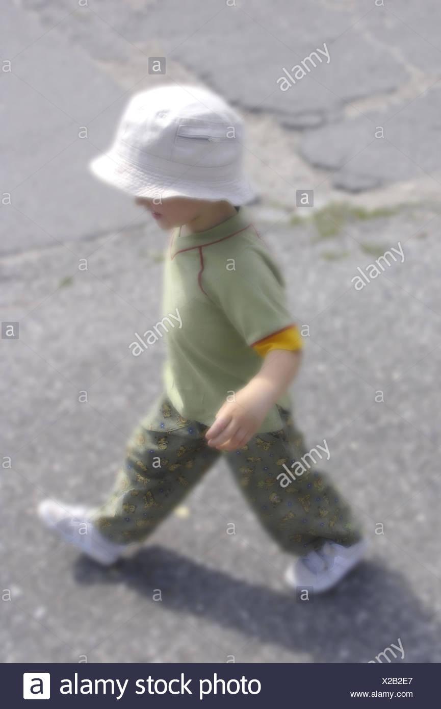 Strasse Junge Seitlich Sonnenhut Aussen Freizeit Freizeitbekleidung Freizeitkleidung Ganzkoerper Gehen Gehend Jugend Kind Kindhe - Stock Image