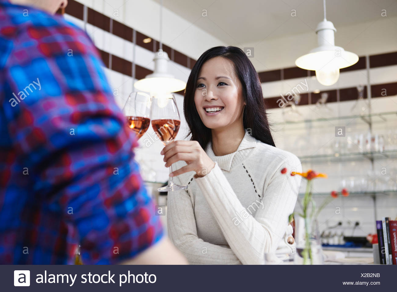 Germany, Cologne, Young couple drinking wine, smiling - Stock Image