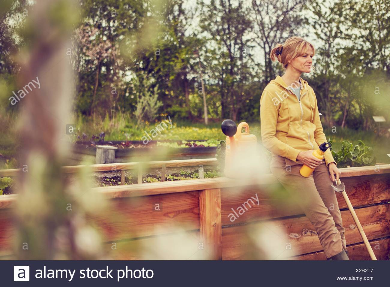 Mature woman, leaning against fence, taking a break from gardening, holding trowel and water bottle - Stock Image