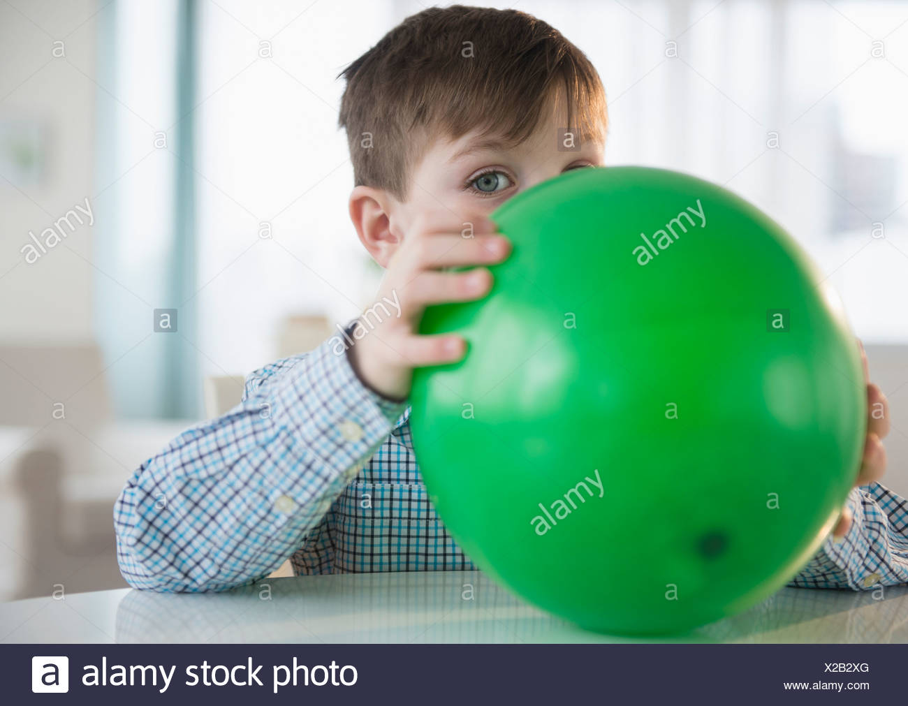 Portrait of boy (4-5) blowing balloon - Stock Image