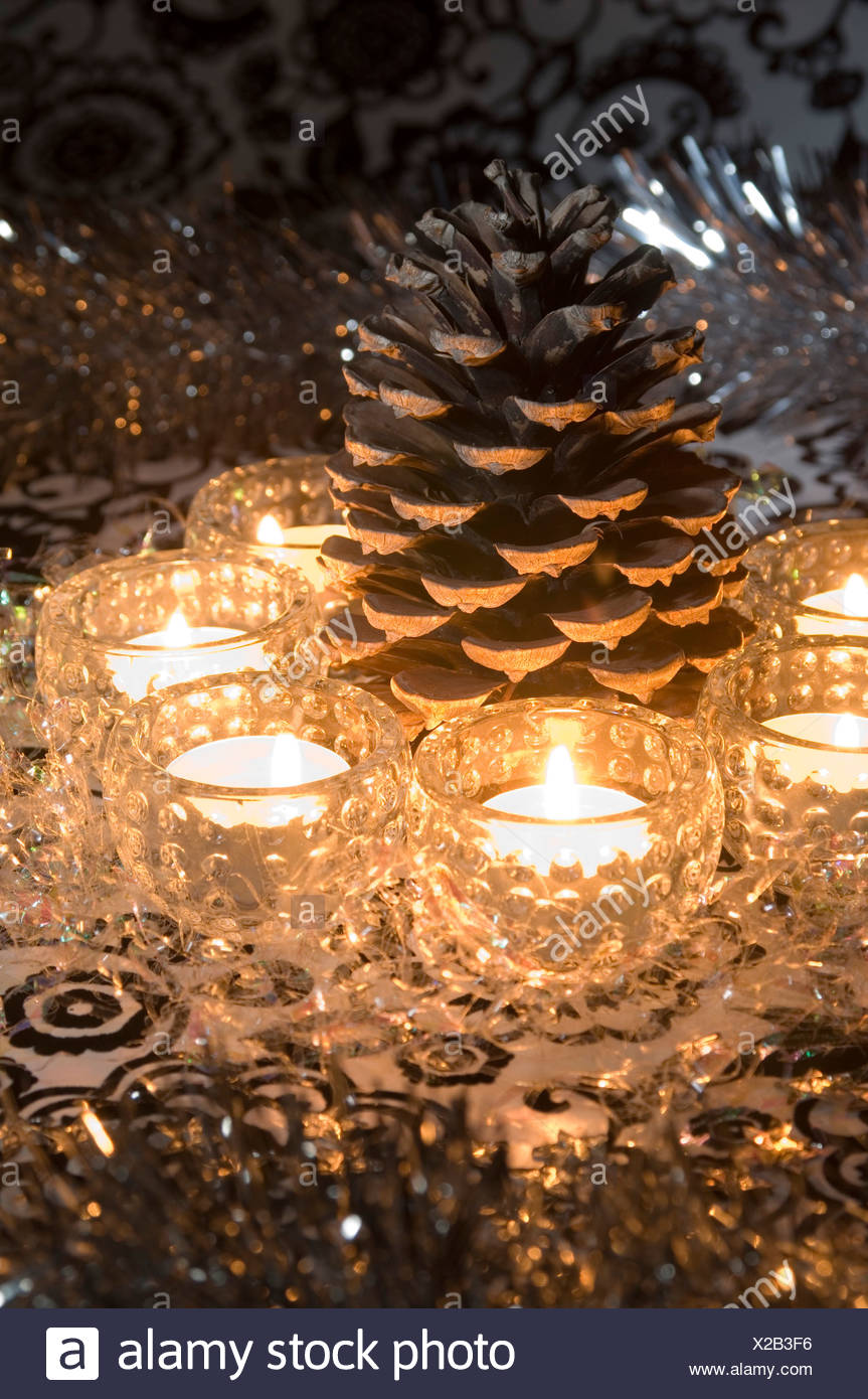 A Still Life Of A Christmas Table Decoration, A Large Pine Cone Surrouned  By Tea Lights In Patterned Glass Jars, Clear