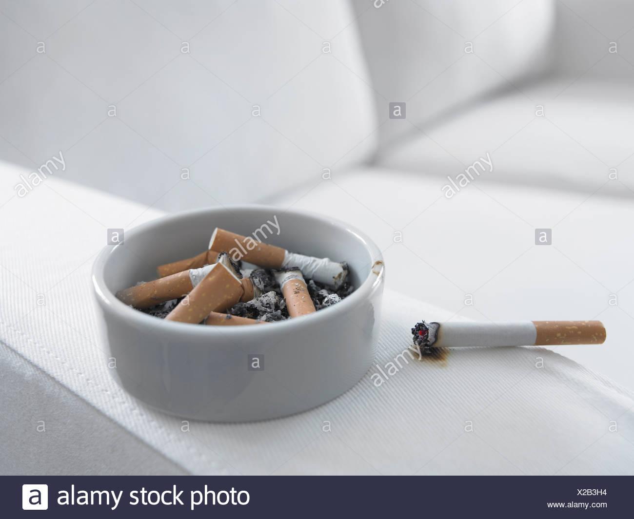 Cigarette burning arm of sofa - Stock Image