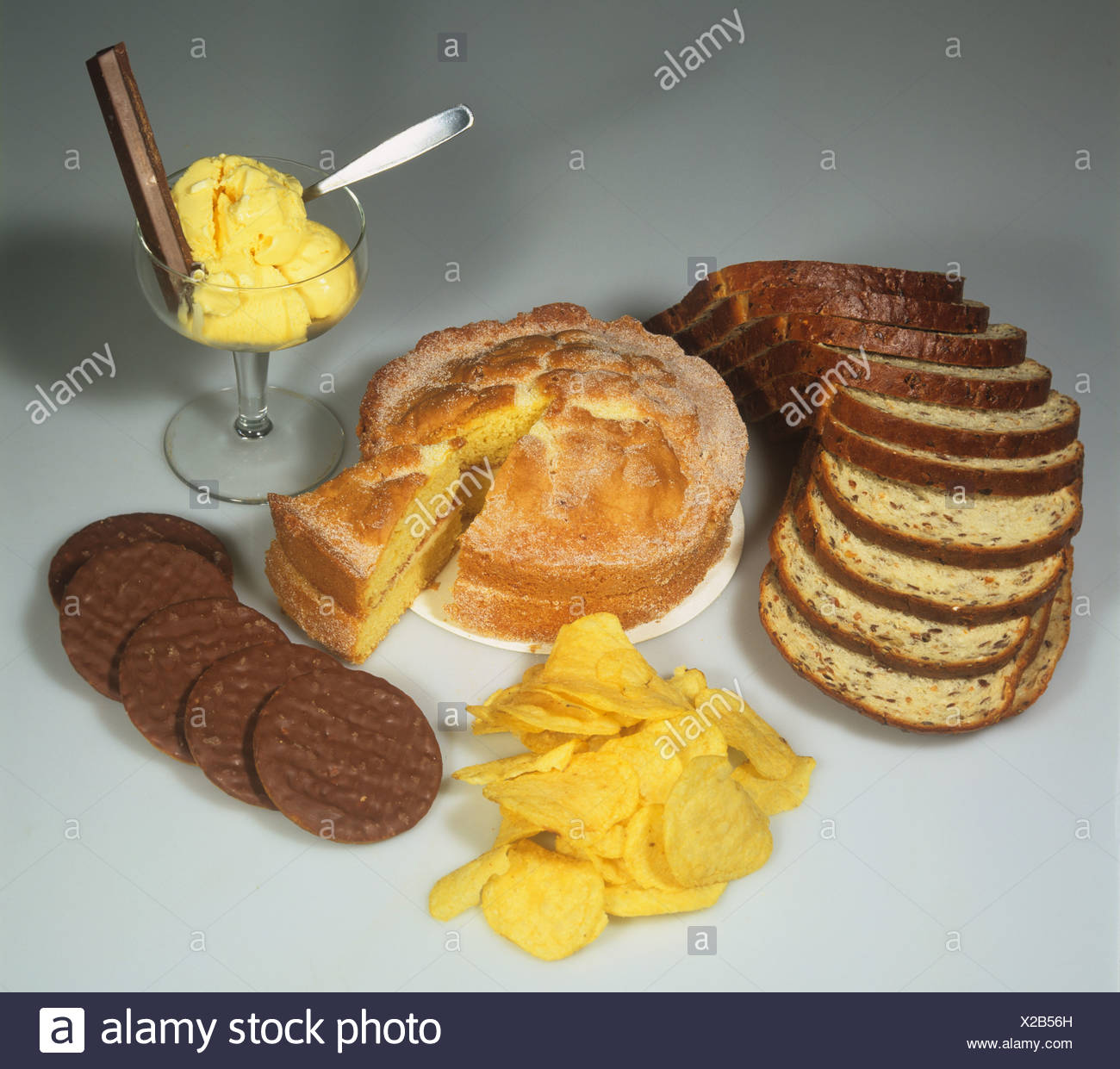 High energy high carbohydrate foods including cake biscuits bread potato crisps chocolate - Stock Image