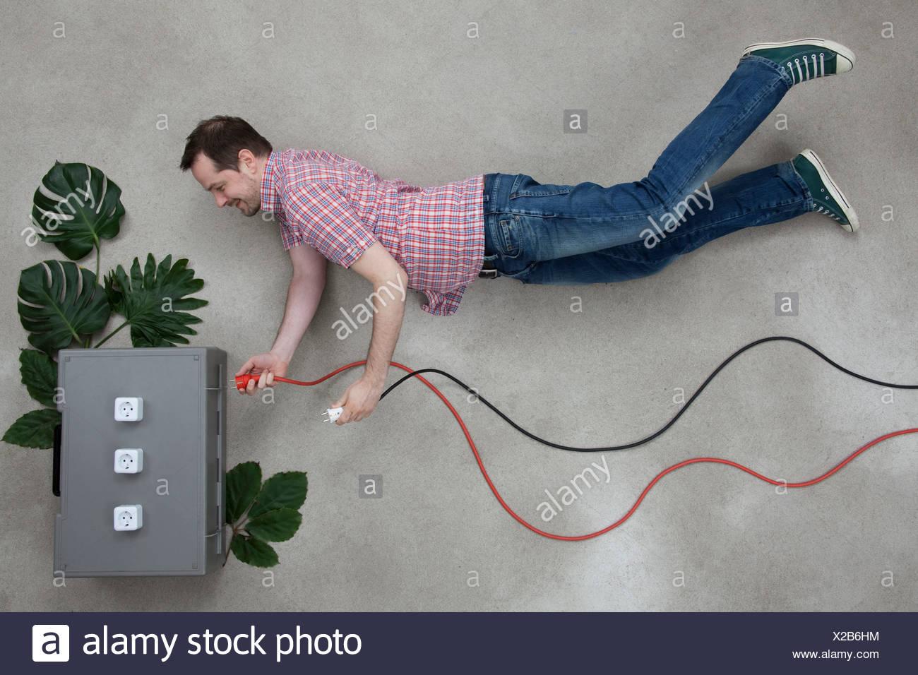 Mid adult man holding plug near electric socket Stock Photo