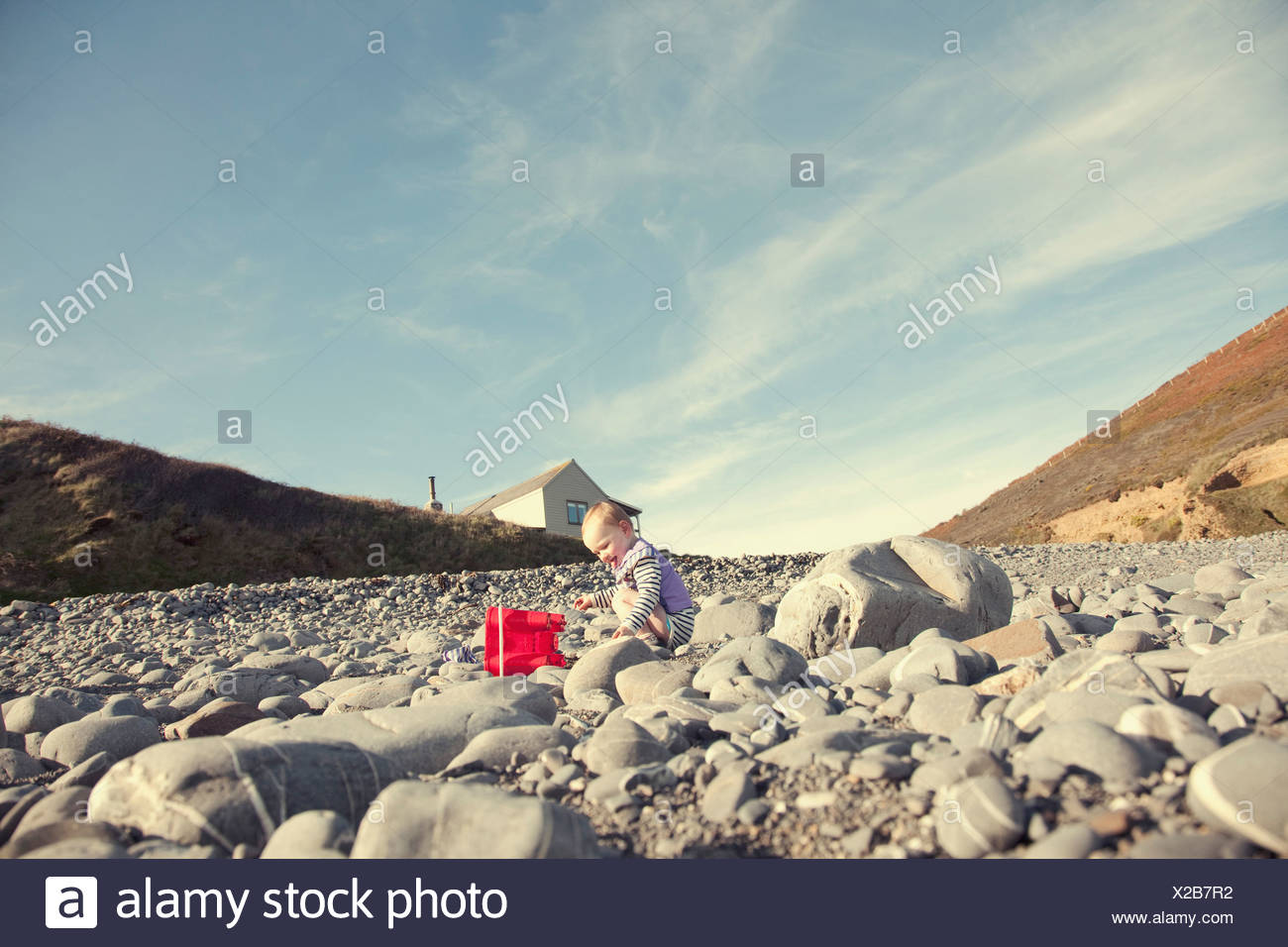 Baby girl playing on beach - Stock Image
