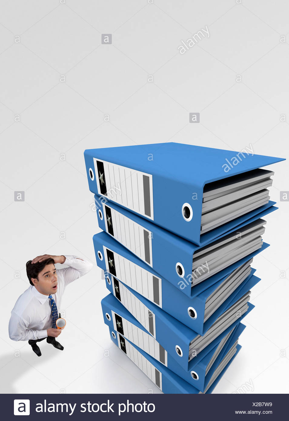 Businessman tensed after looking at a stack of files - Stock Image