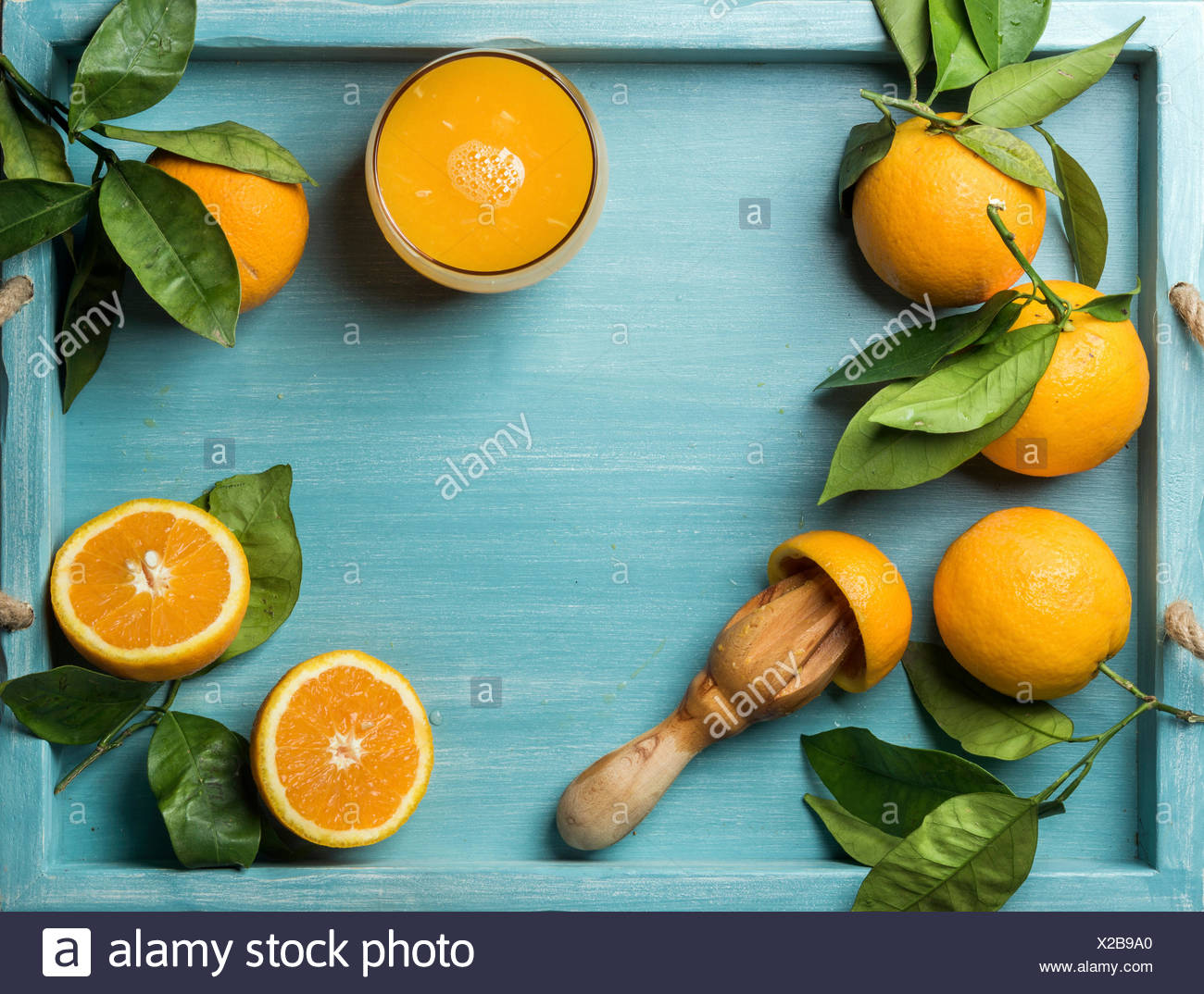 Fresh orange juice in glass and oranges with leaves on wooden turquoise blue painted background. Top view, copy space - Stock Image