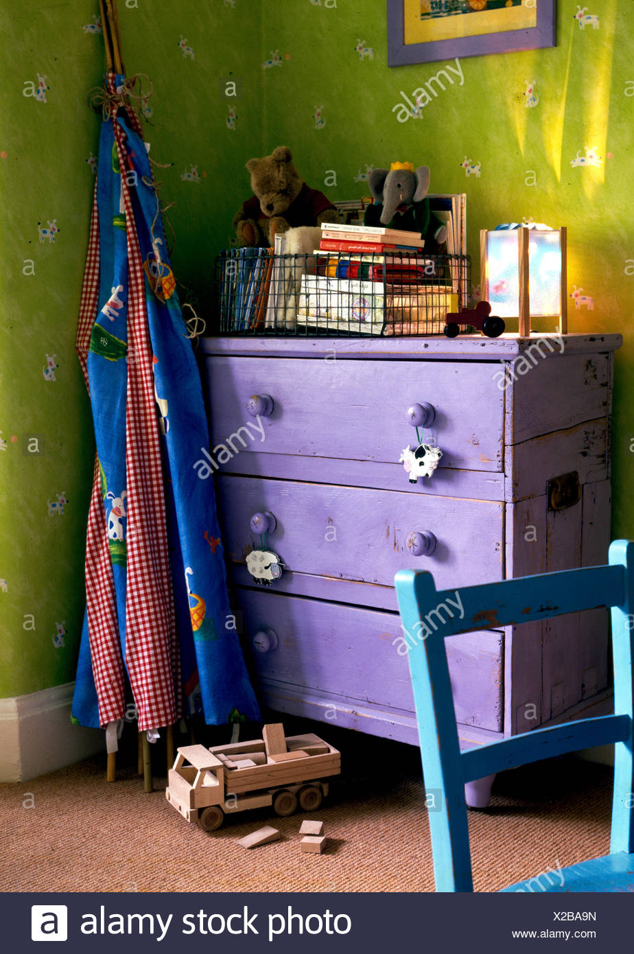 Corner of childrens room with purple painted chest of drawers and folded wigwam Stock Photo