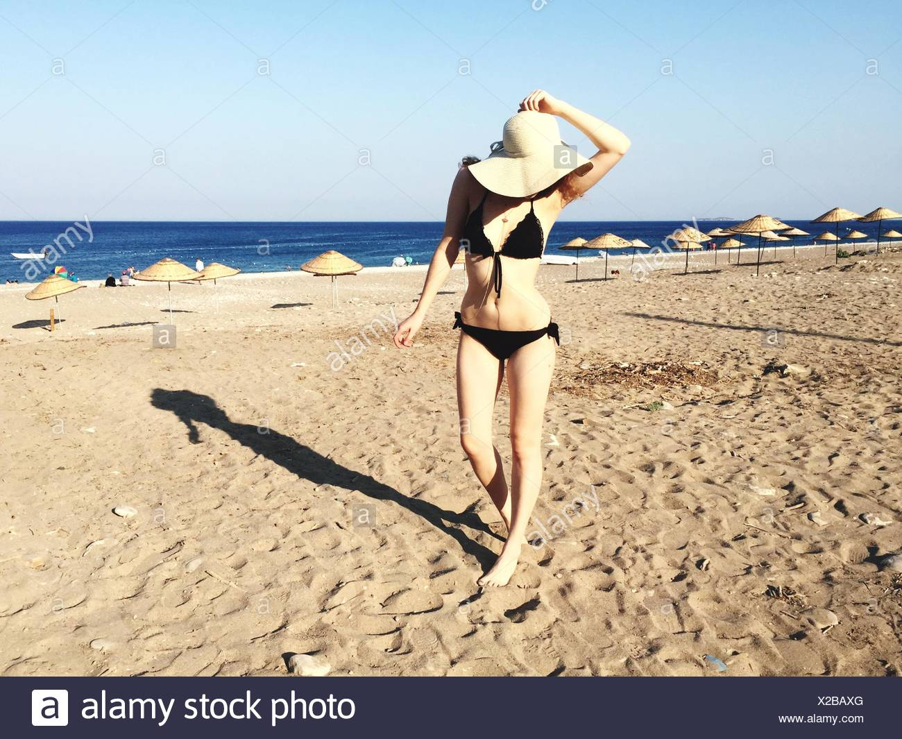 Full Length Of Beautiful Woman In Bikini On Beach During Sunny Day - Stock Image