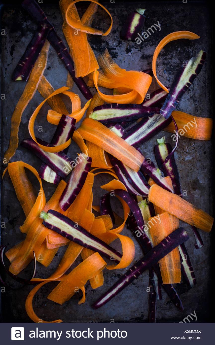 Purple and Orange Carrots, Shaved, on Dark Tray Stock Photo
