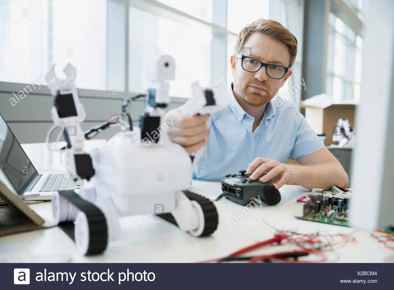 Focused engineer with joystick testing robot - Stock Image