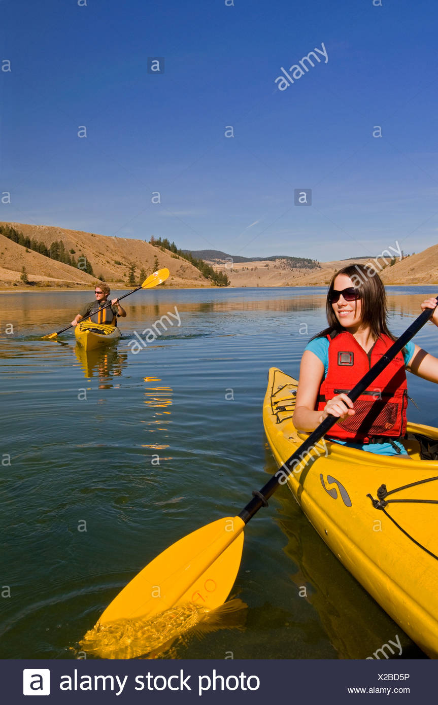 A young couple enjoys a stunning day while kayaking on Trapp Lake, just south of Kamloops, British Columbia, Canada - Stock Image