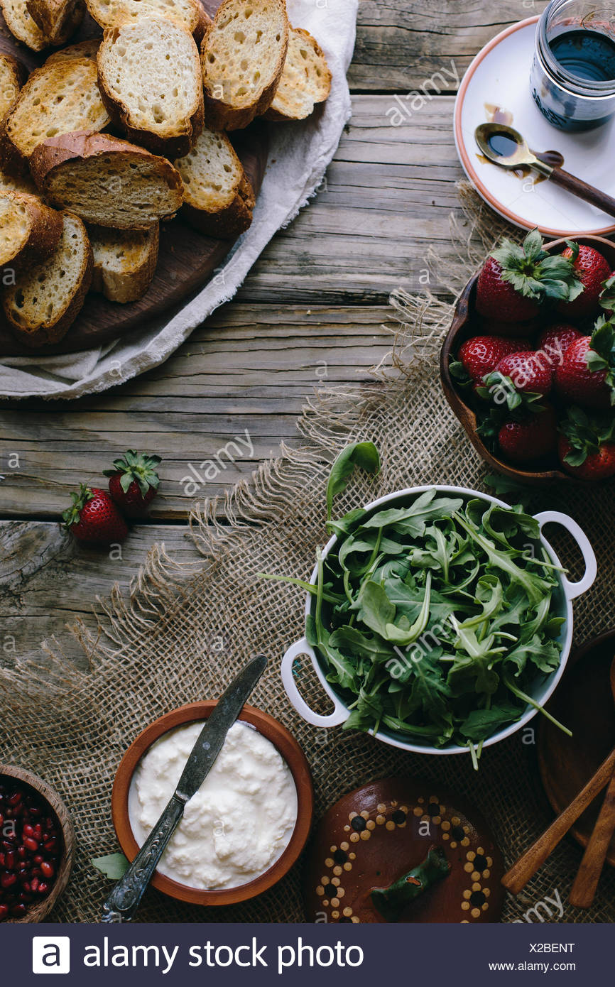 Ingredients for the Strawberry Bruschetta with Balsamic Reduction are displayed on a farm table. - Stock Image