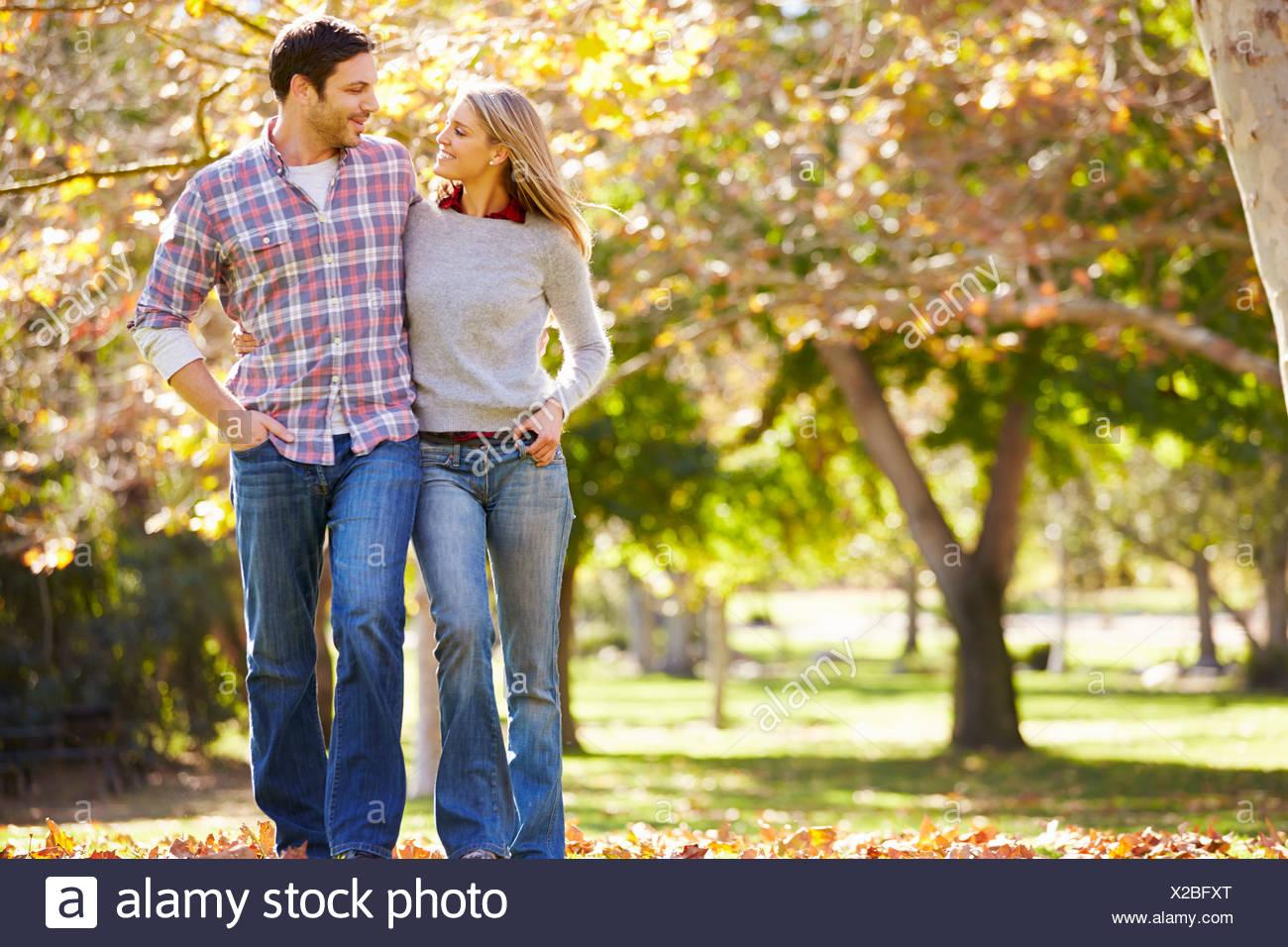 Romantic Couple Walking Through Autumn Woodland - Stock Image