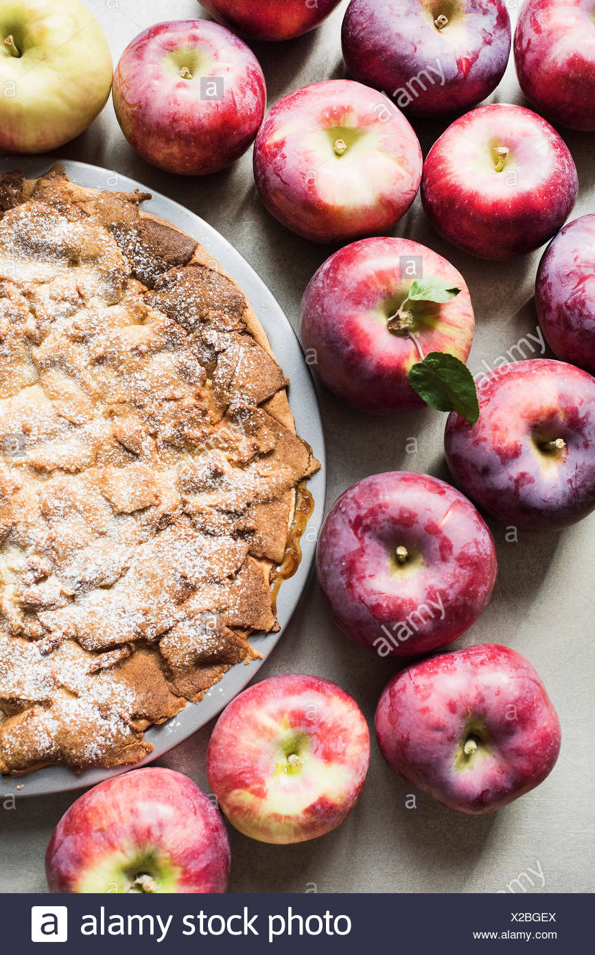 Apple pie with fresh Empire apples, overhead view - Stock Image