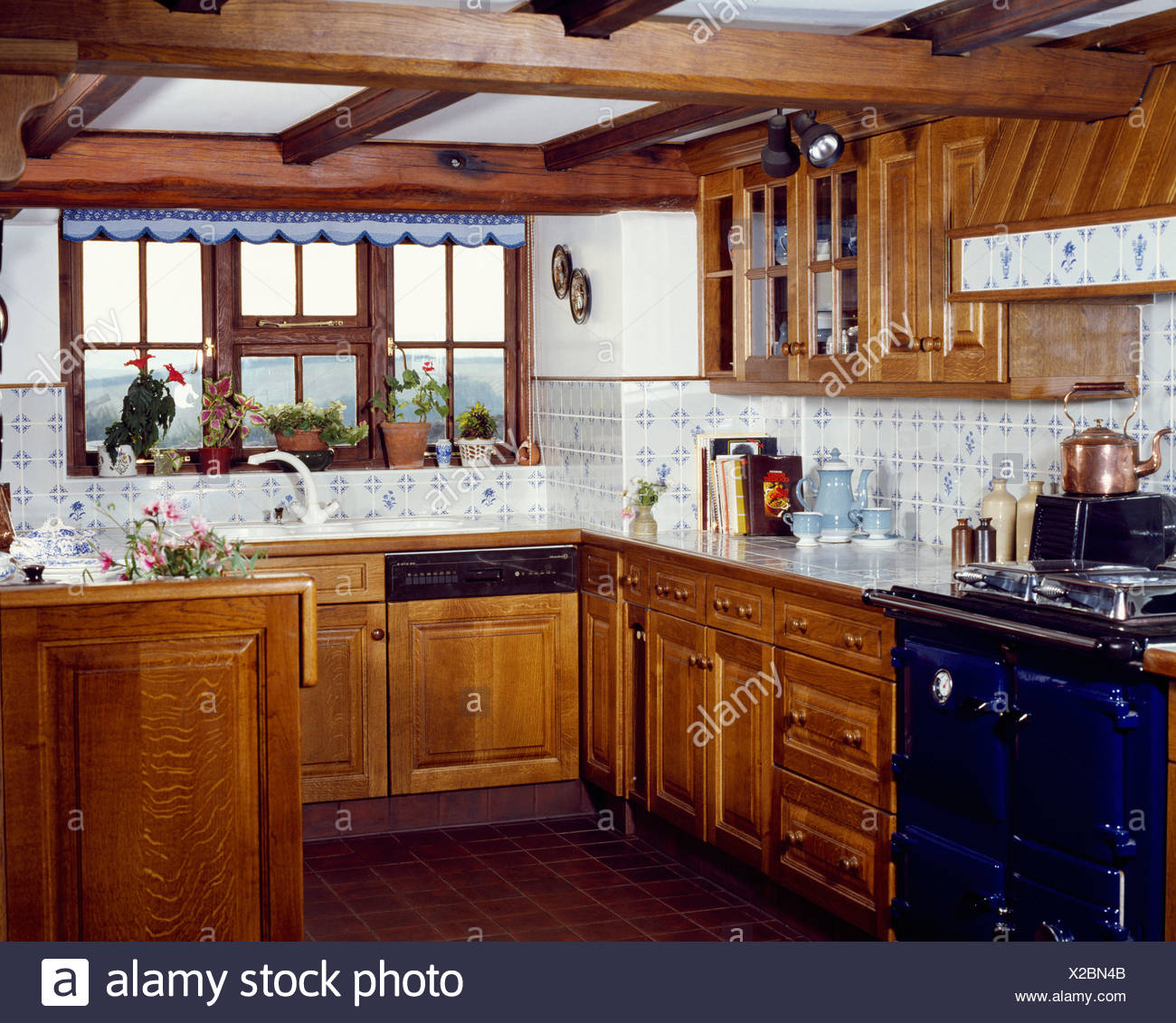 Country Kitchen With Wooden Cupboards And Blue And White Wall Tiles Stock Photo Alamy