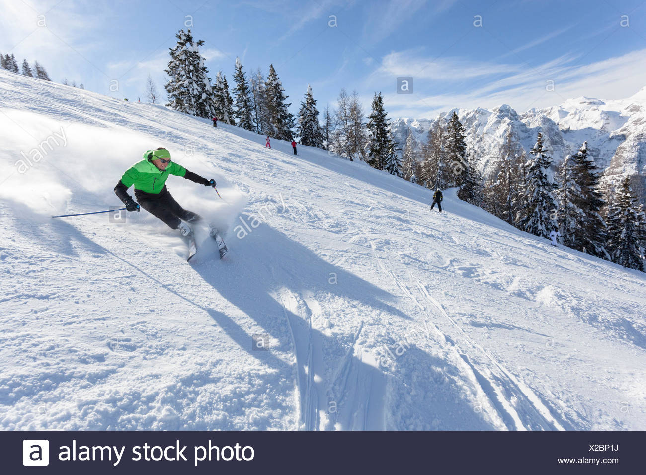 a skier is skiing along the slopes in the Folgarida ski resort with Brenta Group in the background - Stock Image